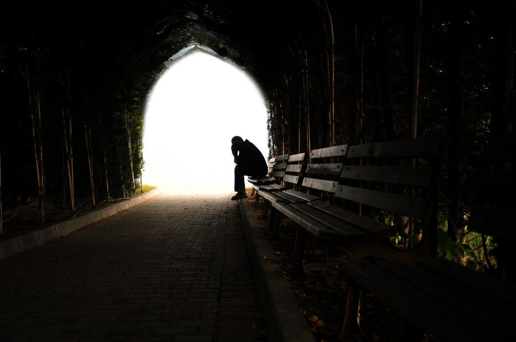 man sitting alone on the bench in the tunnel