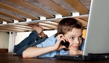 Child playing laptop under the bed. Computer Addiction