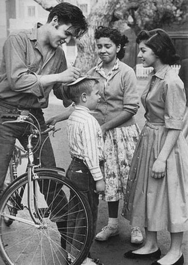 Элвис Пресли дает автограф на голове мальчика.