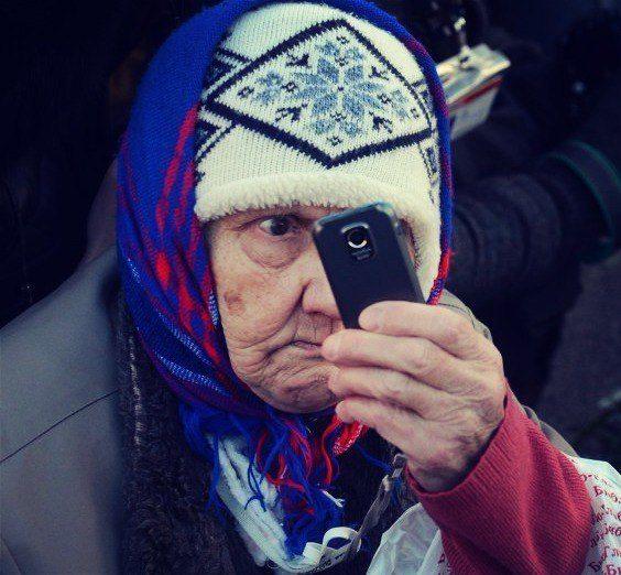 На автобусной остановке древняя старушка с узлом вещей у ног держит в руках мобильник
