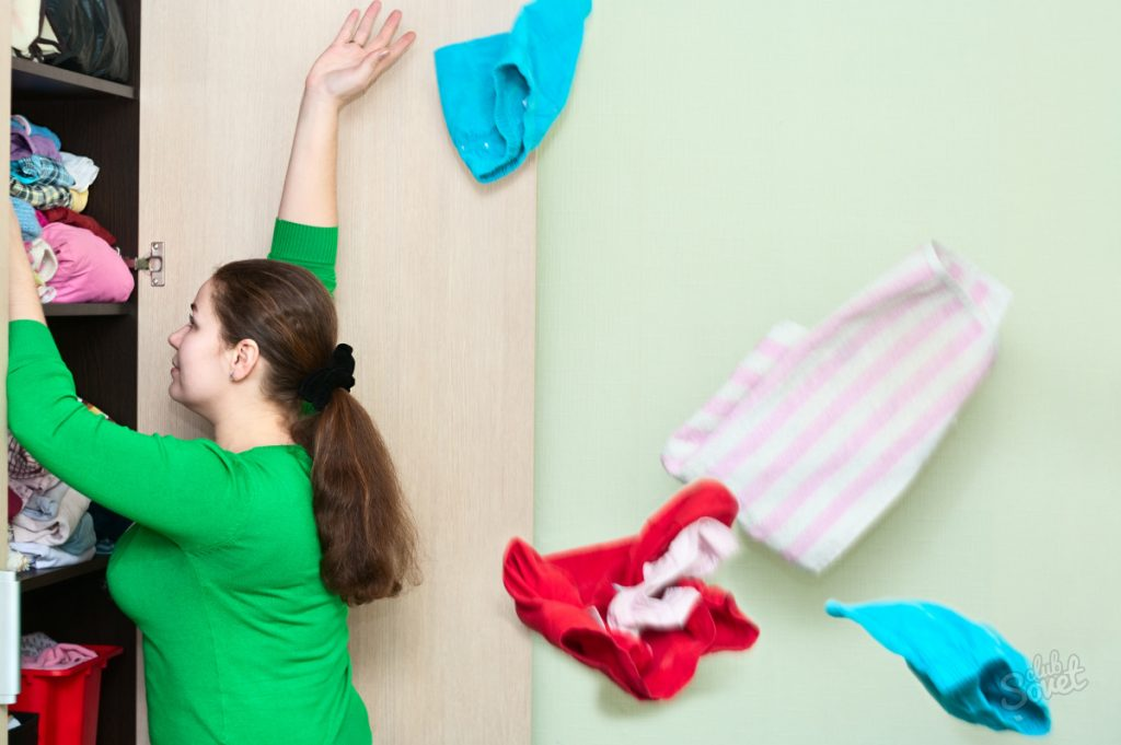 Young caucasian woman throwing a clothes from the wardrobe back.