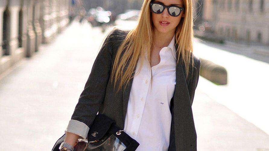 Хорошо одетая молодая женщина идет по улице.