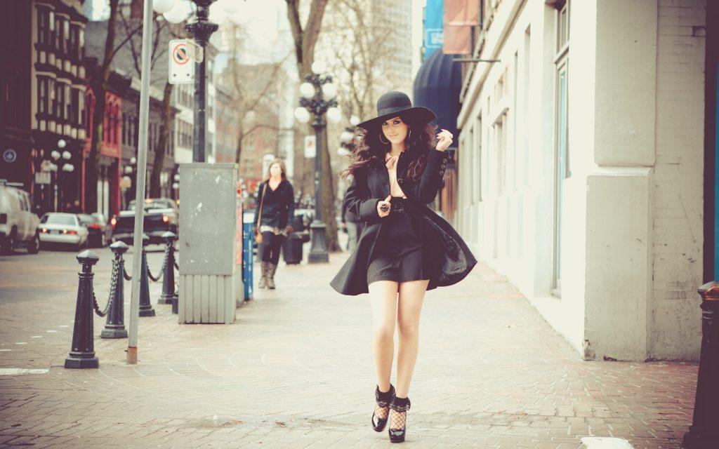 Хорошо одетая молодая женщина идет по улице...