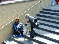 В переходе возле станции метро сидит женщина неопределенного возраста.