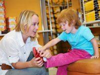 Воспитатель в детсаде помогает мальчику натянуть ботинки…..