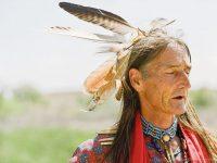 Два ковбоя встретили индейца, лежащего на животе и прислонившись ухом к земле.